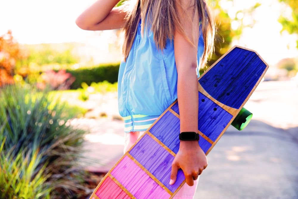 Fitbit_Ace_3_Lifestyle_Black_Sidewalk_with_Skateboard_051